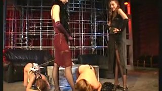 Two mistresses dominate their caged slave girl