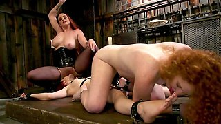 Dominant lesbians have fun with a curly redhead in the dungeon
